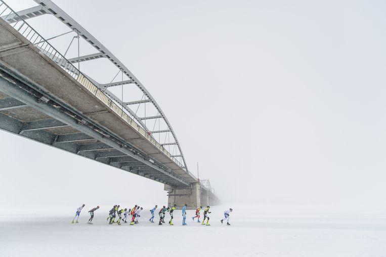 De latere winnaar Simon Schouten passeert als eerste de brug tijdens de marathon op natuurijs in het Zweedse Lulea. Beeld Vincent Riemersma