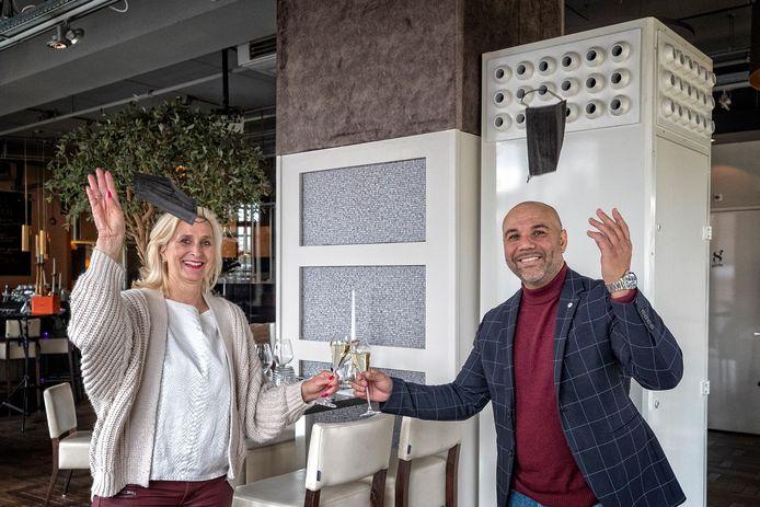 'Weg met die mondkapjes': Chantal Roeleveld (Grand Café Eight) en StaticAir-directeur Steven Finsy proosten op de plaatsing van de luchtbehandelingsmachine die virussen en bacteriën zou doden.