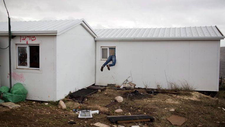 Een kolonist klimt een van de leeggehaalde woningen in de nederzetting Amona binnen. Beeld epa