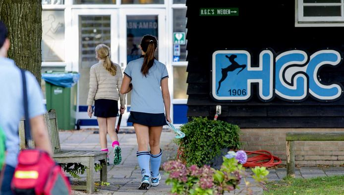 Leden van de hockeyclub HGC komen aan bij het clubgebouw met aan de rechterkant de kleedkamers