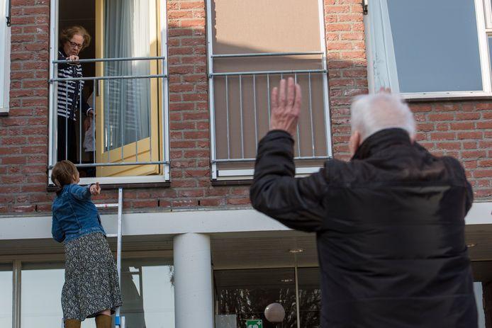Ton Wientjen zwaait naar zijn vrouw Truus bij woonzorgcentrum Antonius in Acht. Op de trap hun dochter Margot.