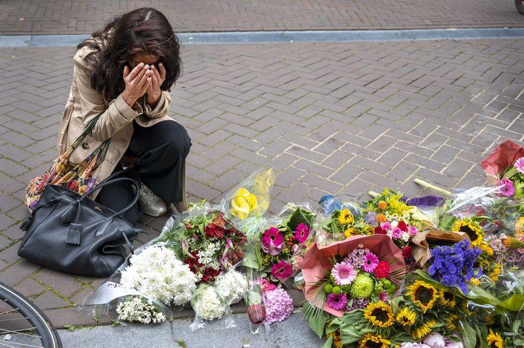 Mensen laten bloemen, kaarsjes en steunbetuigingen aan Peter R. de Vries achter in de Lange Leidsedwarsstraat in het centrum van Amsterdam. Beeld ANP