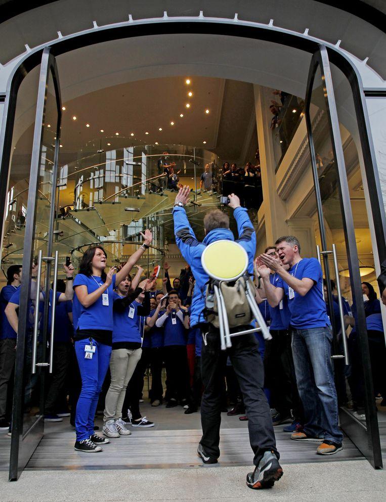Onder luid applaus van het personeel betreedt een van de eerste klanten de nieuwe Apple Store. © ANP Beeld