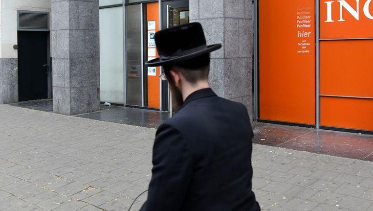 Een Joodse man loopt voorbij een vestiging van ING in Antwerpen. Beeld HH