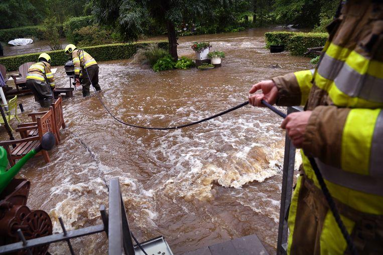 Brandweermannen proberen te voorkomen dat spullen door de snelstromende Geul worden meegenomen. Beeld Marcel van den Bergh / de Volkskrant