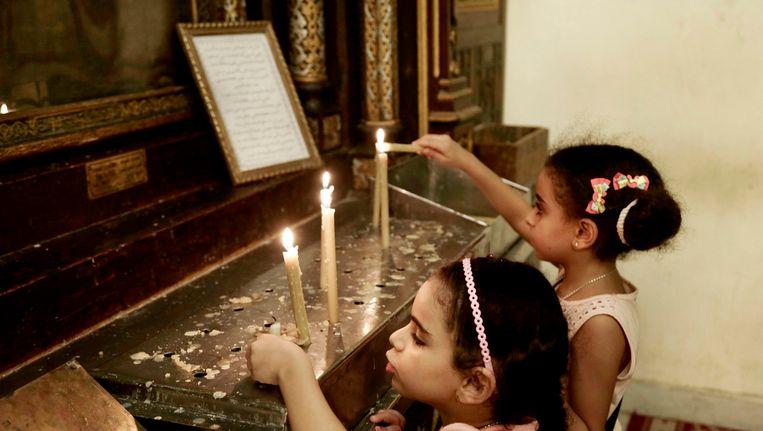 Twee christelijke Egyptische meisjes steken een kaarsje op in een kerk in Oud-Caïro. Beeld AP