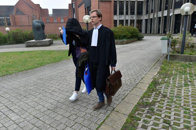 Candide H. verstopt zich bij het buitenkomen van het gerechtsgebouw in Brugge onder haar jas.