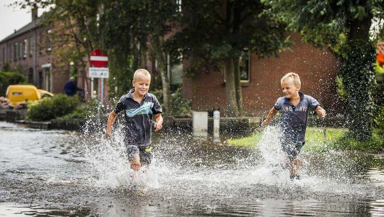 Jongetjes rennen door een ondergelopen straat in Kockengen. Beeld anp