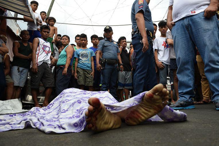 Politieagenten en omstanders bij het toegedekte lichaam van een bij een anti-drugsoperatie doodgeschoten verdachte in Manila, 2016. Beeld AFP