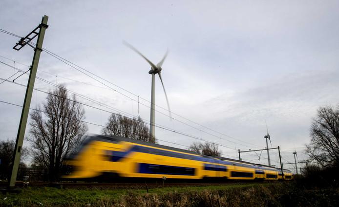 Een NS-trein passeert een windmolen
