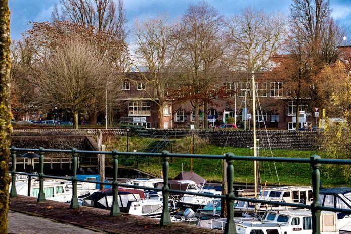 De voormalige meisjesvakschool, met op de voorgrond de Vispoorthaven.