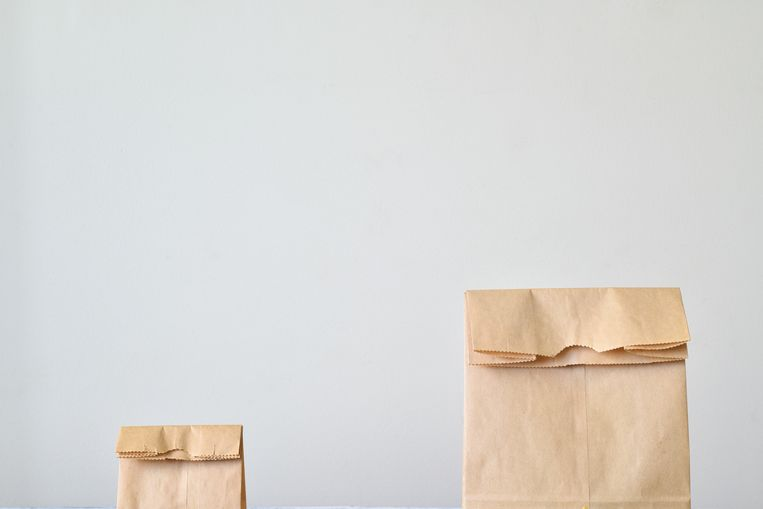 The top portion of a small paper bag and a large paper bag folded at the top. Beeld Getty Images/iStockphoto