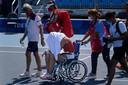 Paula Badosa wordt per rolstoel van de baan geholpen.