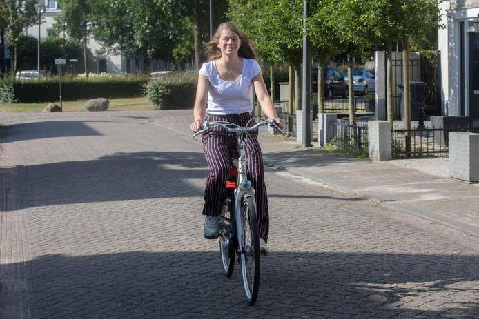 Fabiënne Wachters uit Helmond fietst door haar straat in Brandevoort.