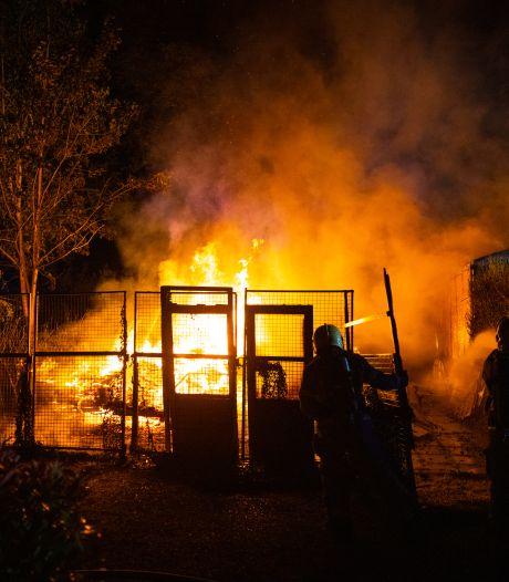 Vlammen slaan metershoog uit houthok met oldtimers op camping bij Epe