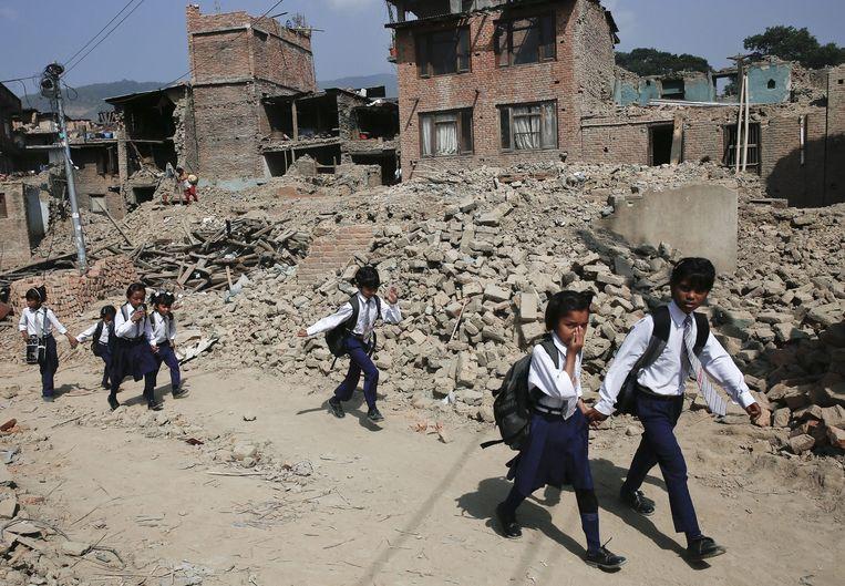 Kinderen in Kathmandu lopen tussen de verwoeste huizen naar school. Beeld epa