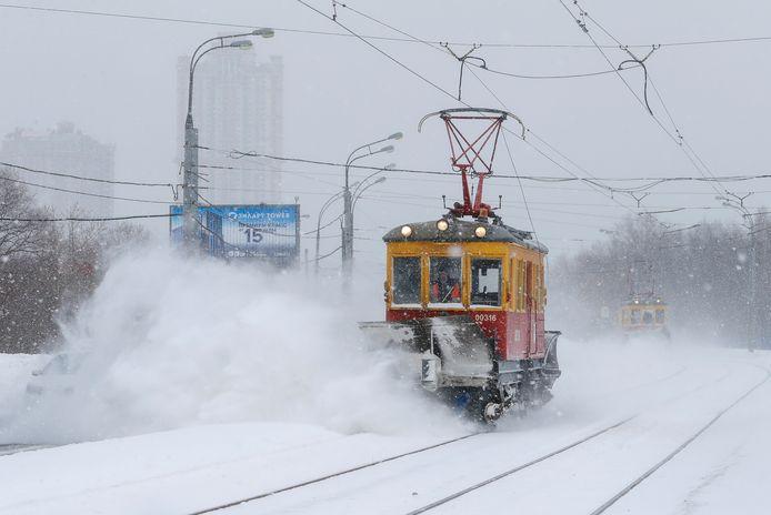 Een onderhoudstram probeert sneeuw weg te duwen.