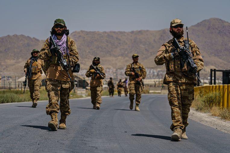 Talibanstrijders op patrouille rond de luchthaven van Kaboel.  Beeld Photo News