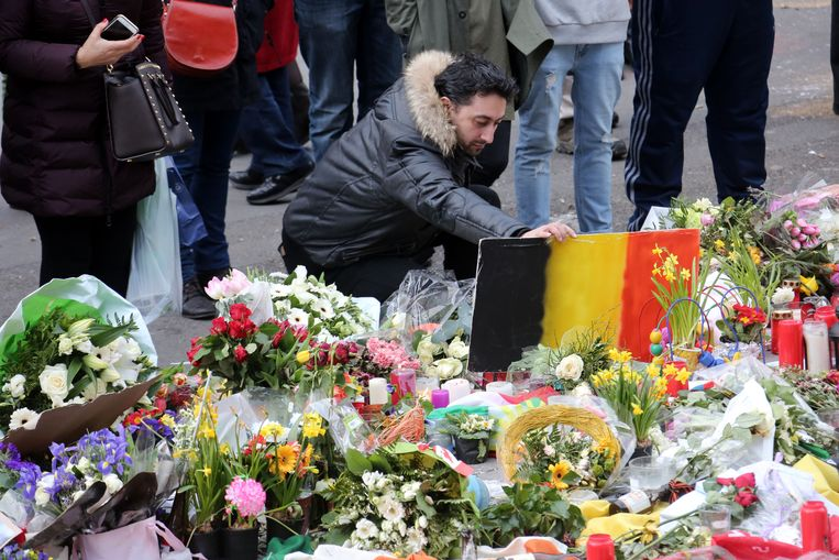 Mensen leggen bloemen, kaarsen en Belgische vlaggen neer aan de Beurs. Beeld Getty Images