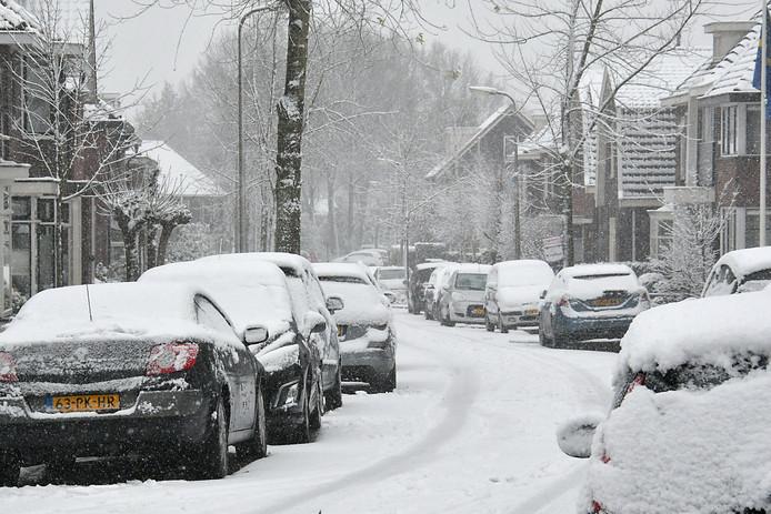 Met sneeuw bedekte auto's in Oldenzaal