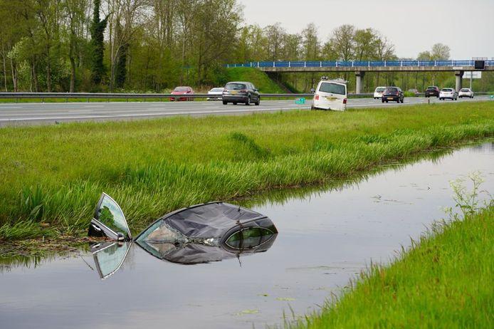 De personenauto (voorgrond) kwam naast de A28 in het water na een botsing met het witte bestelbusje (achtergrond).