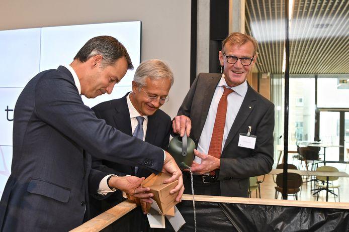 Premier Alexander De Croo geeft symbolisch wat aarde uit zijn tuin in de Vlaamse Ardennen aan de 'rootbox' binnen het gloednieuwe Rootbox-hoofdkwartier van Ardo.