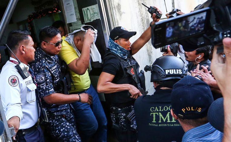 Een van de drie agenten wordt uit de rechtszaal geëscorteerd nadat hij schuldig werd bevonden van de moord op de 17-jarige Kian delos Santos.   Beeld AP