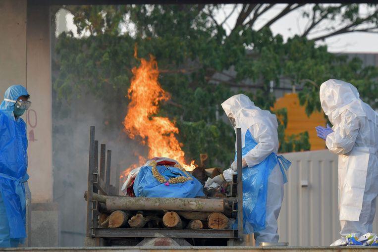 Overleden slachtoffers van de pandemie worden in Bangalore in openlucht gecremeerd.  Beeld AFP