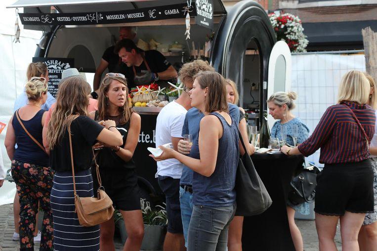 De bezoekers proeven allerlei hapjes op het Foodtruck Festival