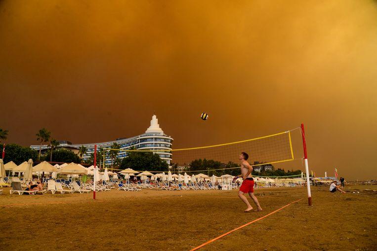 Donkere rookwolken pakken zich samen boven een beachvolleybalveld in de Turkse badplaats Manavgat, niet ver van de populaire toeristenplek Antalya. Beeld AFP