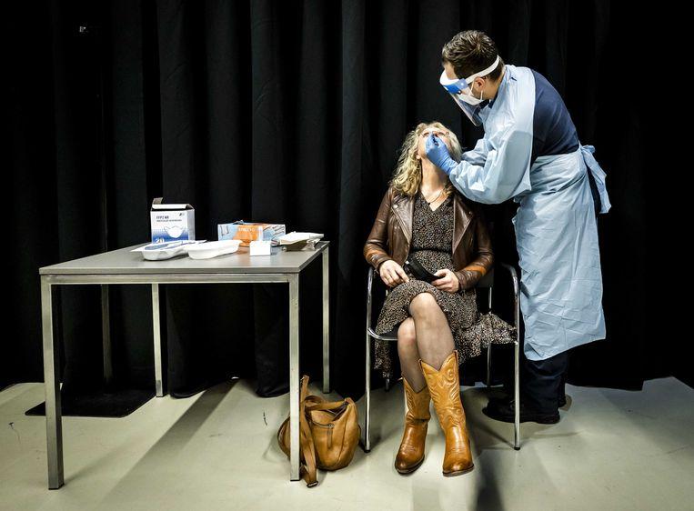 Een bezoeker laat zich testen op het coronavirus voorafgaand aan de voorstelling van cabaratier Guido Weijers. Beeld ANP