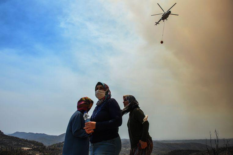Een helikopter giet water  over de vlammen in Sirtkoy, Antalya. Beeld AP