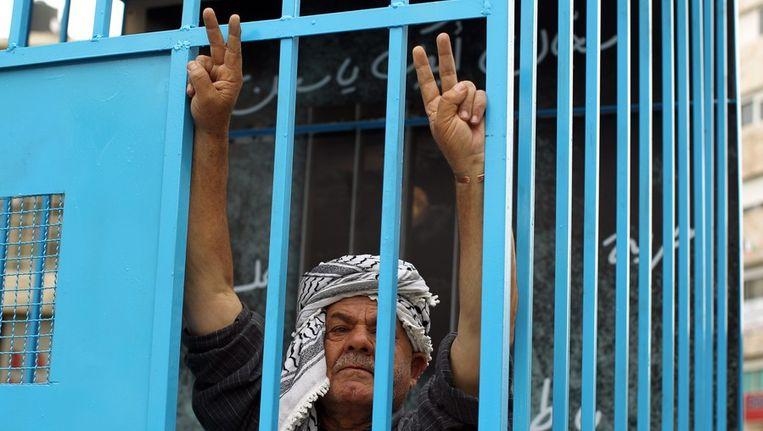 Een Palestijnse demonstrant in een symbolische kooi in Ramallah. Beeld epa