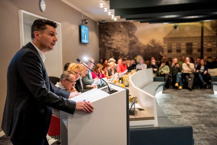 Ouder Martijn Loos voert het woord. Op de publieke tribune luisteren andere ouders toe.