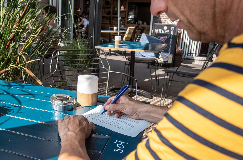 Een klant op een terras in Groesbeek vult zijn persoonsgegevens op een formulier in.