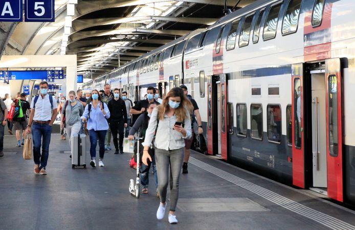Passagiers met mondmaskers in het centraal station van Zürich.