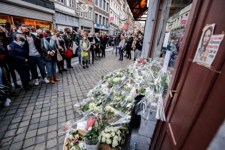 Omstanders leggen bloemen neer bij de kapsalon van Alysson Jadin in Luik. De 24-jarige kapster stapte uit het leven nadat haar pas geopende zaak verplicht moest sluiten door de lockdown.  Beeld EPA