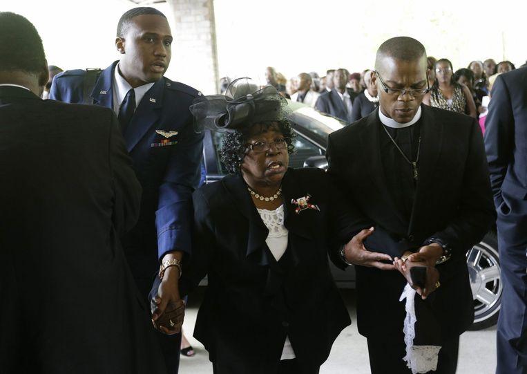 Judy Scott (midden) wordt naar de kerk begeleid voor de afscheidsdienst van haar zoon. Beeld epa