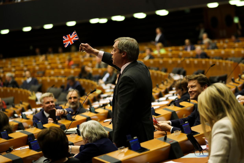 De Britse europarlementariër Nigel Farage zwaait met de Britse Union-vlag tijdens een toespraak in de plenaire vergadering woensdag.  Beeld AP