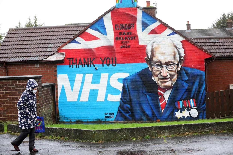 Een vrouw wandelt langs een muurschildering van Captain Tom Moore, die meer dan een miljoen pond inzamelde voor gezondheidszorgstelsel NHS. Beeld AP