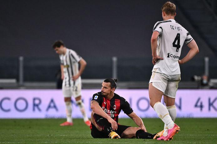Zlatan Ibrahimovic zit op de grond. Matthijs de Ligt kijkt toe.