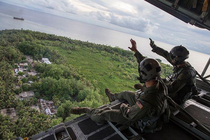 Amerikaanse soldaten tzwaaien naar de inwoners van Manoluk tijdens een humanitaire hulpdropping in december 2015.