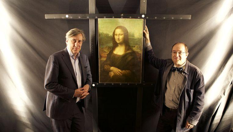 Andrew Graham-Dixon (links) en Pascal Cotte naast een afbeelding van de Mona Lisa. Beeld BBC/Brinkworth Films/Richard Ranken