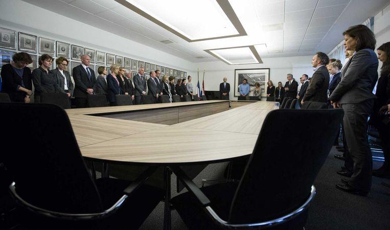De Nederlandse ambassadeur Ed Kronenburg en medewerkers van de ambassade tijdens de minuut stilte. Beeld anp
