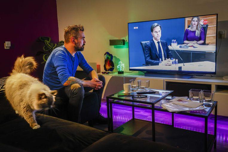 Een gedupeerde ouder volgt het verhoor van premier Mark Rutte door de parlementaire ondervragingscommissie. Beeld ANP