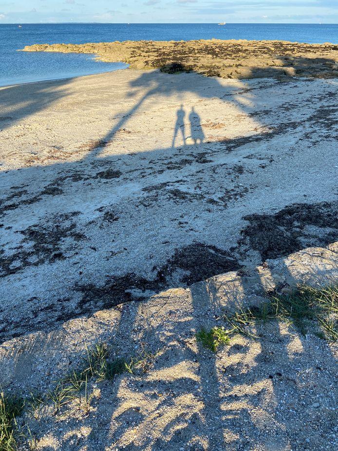 VREEMDE GEWAARWORDING - De ondergaande zon op het strand van Quiberon in Bretagne in Frankrijk in de rug van Ernst Steffens en zijn vrouw zorgt voor lange schaduwen. Vandaar de lange benen op de voorgrond.