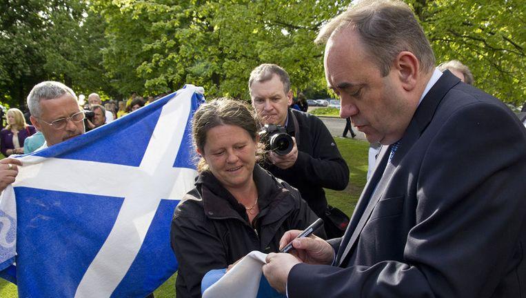 De Schotse eerste minister Alex Salmond (R) zet zijn handtekening op de Schotse nationale vlag Beeld