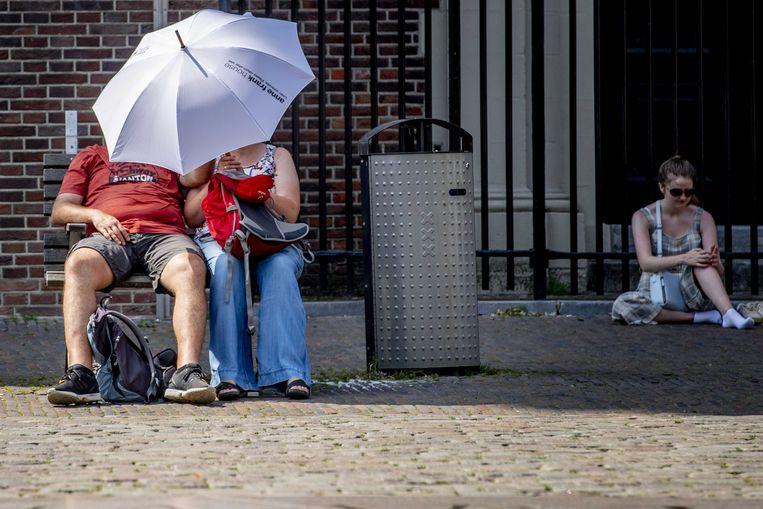 AMSTERDAM - Een paraplu tegen de zon als bescherming tegen de hitte. Het KNMI gaf vorig jaar zomer code oranje af wegens de extreme warmte. Beeld ANP / ROBIN UTRECHT