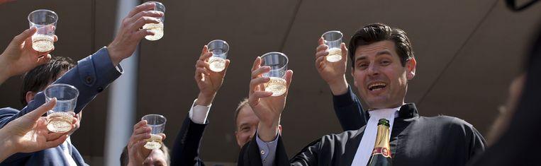Advocaat Roger Cox en Urgenda heffen het glas op de overwinning. Beeld AP