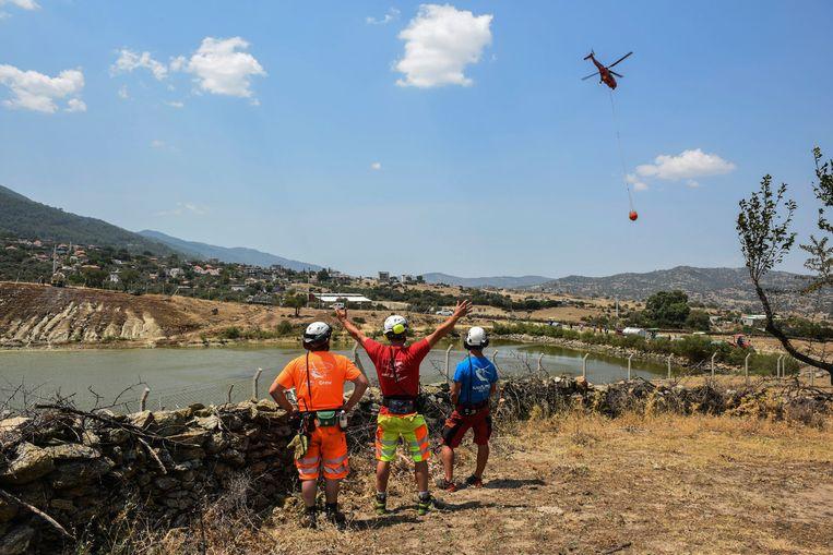 Een helikopter neemt water mee uit een meer nabij Cine, in de provincie Aydin.   Beeld AP